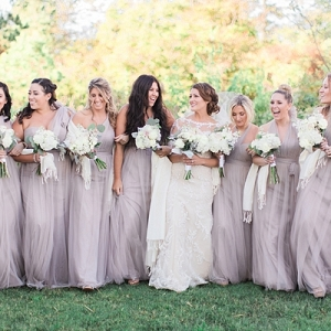 Bridesmaids in neutral purple dresses