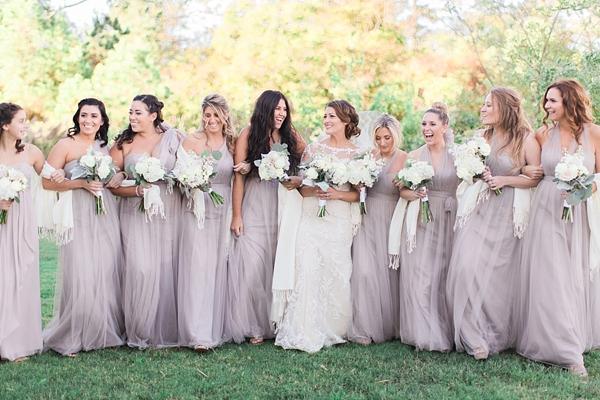 Bridesmaids in neutral purple dresses