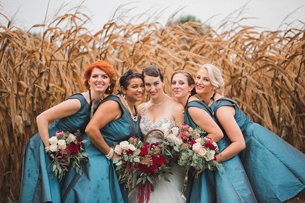 Bridesmaids in teal dresses in wheat field
