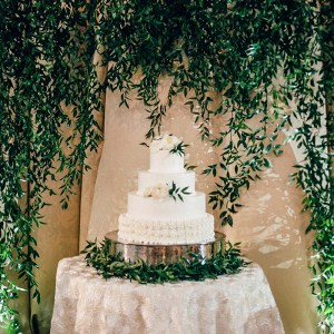Beautiful Greenery Backdrop behind Textured Wedding Cake