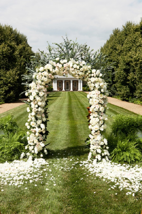 Oversized all white rose flower arch from home ceremony